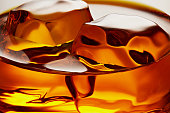 Glass of elegant whiskey with ice cubes. Macro closeup view