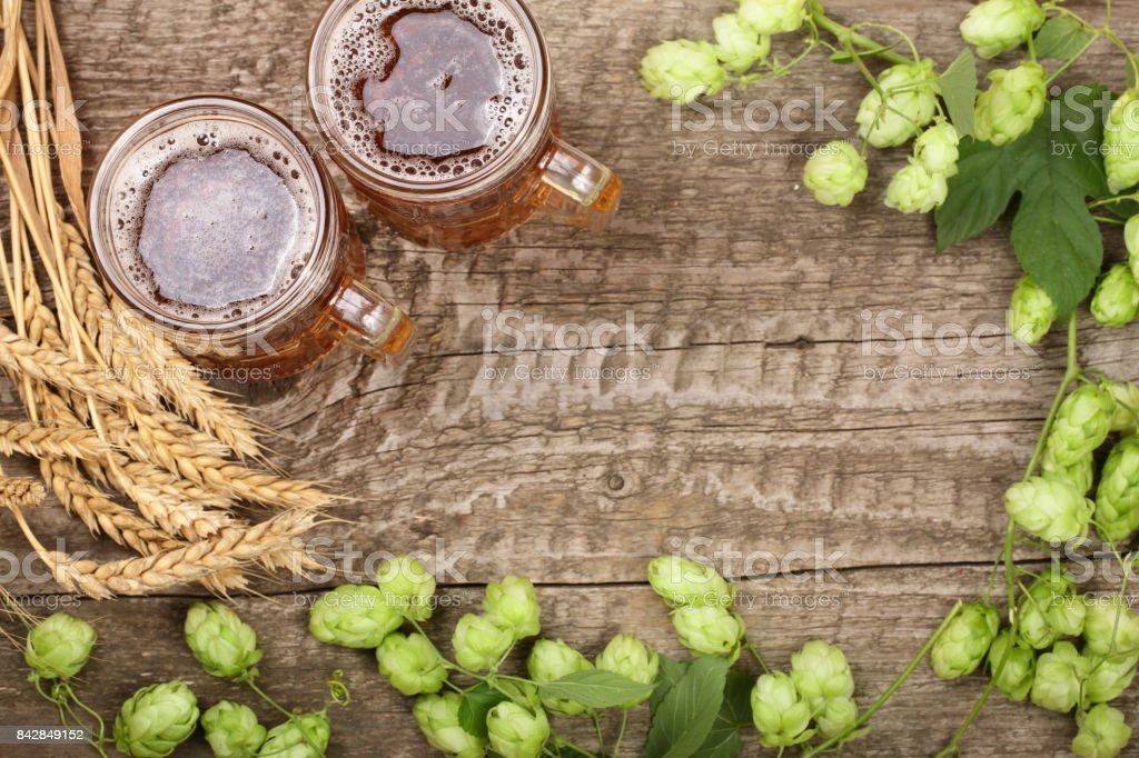 glass of foamy beer with hop cones and wheat on old wooden background. Top view with copy space for your text stock photo