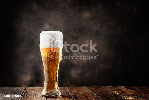 istock Glass of fresh and cold beer on dark background 1058117688