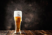 Glass of fresh and cold beer on dark background