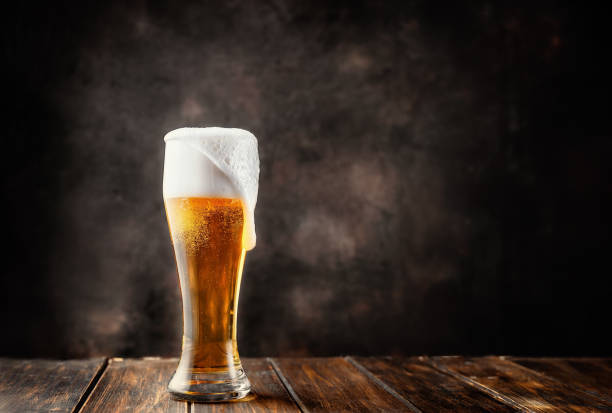 glass of fresh and cold beer on dark background - beer alcohol stock pictures, royalty-free photos & images