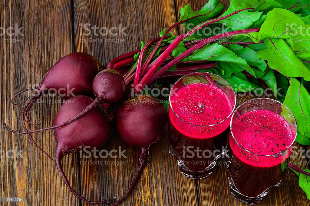 Glass of fresh beetroot juice with bets on wooden table stock photo