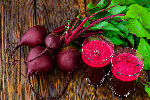 Glass of fresh beetroot juice with bets on wooden table Glass of fresh beetroot juice with bets on wooden table. beet stock pictures, royalty-free photos & images