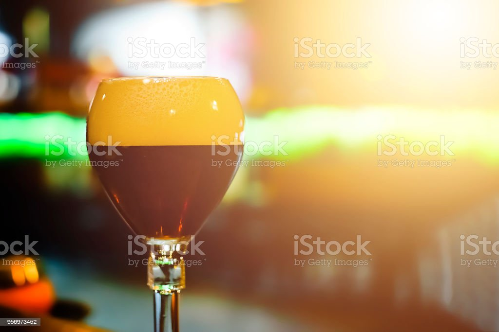 Glass of fresh dark beer on rustic pub background. stock photo