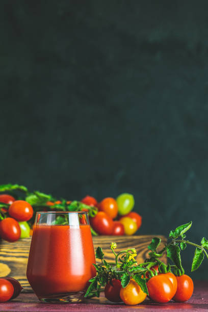 Glass of fresh delicious jummy red tomato juice and fresh tomatoes in wooden box. Dark background. Close up. Gmo free. Natural good food stock photo