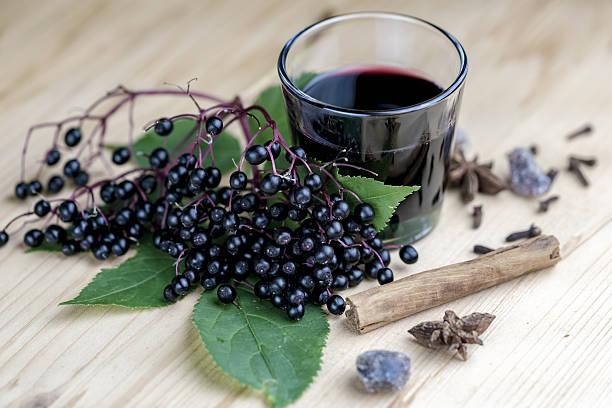 glass of fresh elderberry syrup with ingredients - xarope imagens e fotografias de stock