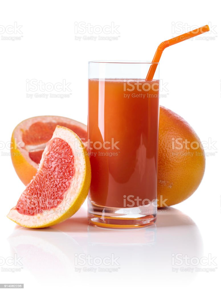 Glass of fresh grapefruit juice and cut fruits white background. stock photo