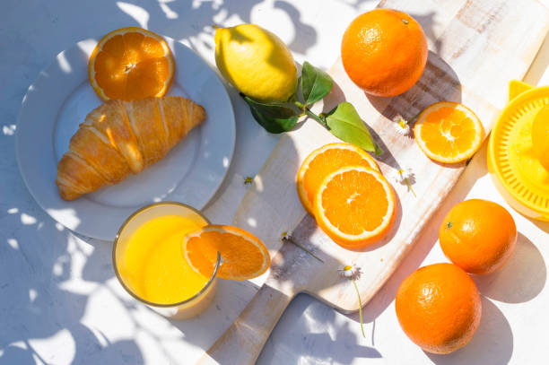 A glass of fresh orange juice, croissant breakfast, lemons and oranges in the morning sunlight and tree shadow on white background stock photo