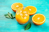 A glass of fresh orange juice with orange halves and green leaves on a vibrant blue background with a place for text