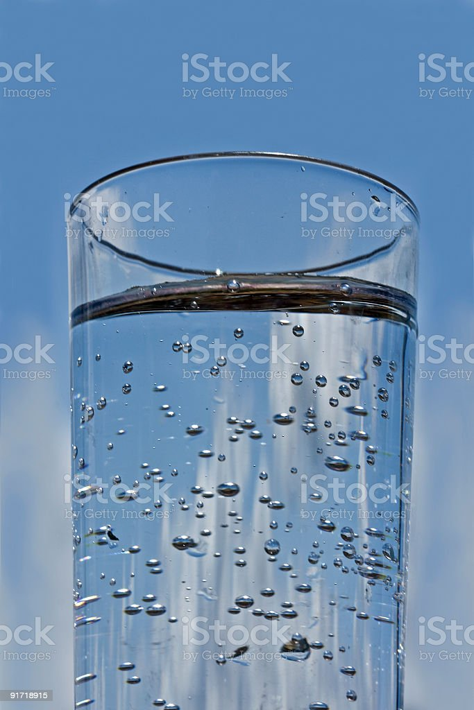 Glass of fresh sparkling water against a blue sky royalty-free stock photo