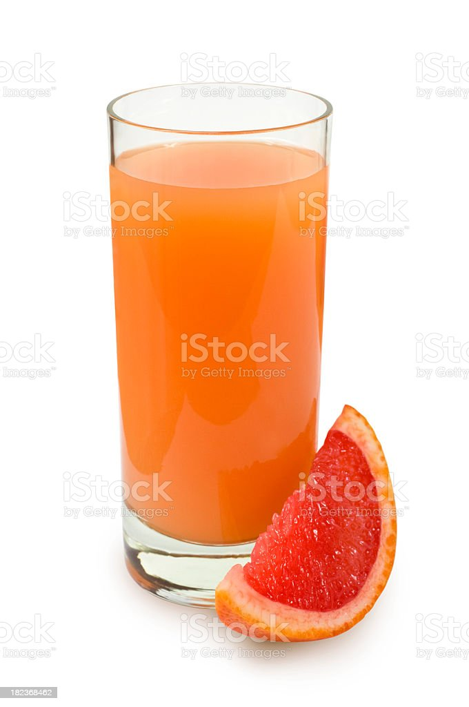 Glass of fresh squeezed grapefruit juice next to a wedge stock photo
