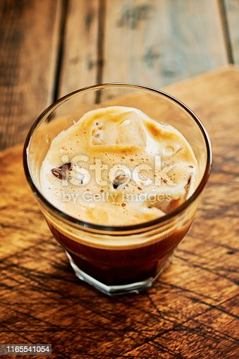 Glass of freshly brewed espresso coffee over ice, served against a rustic wood surface.