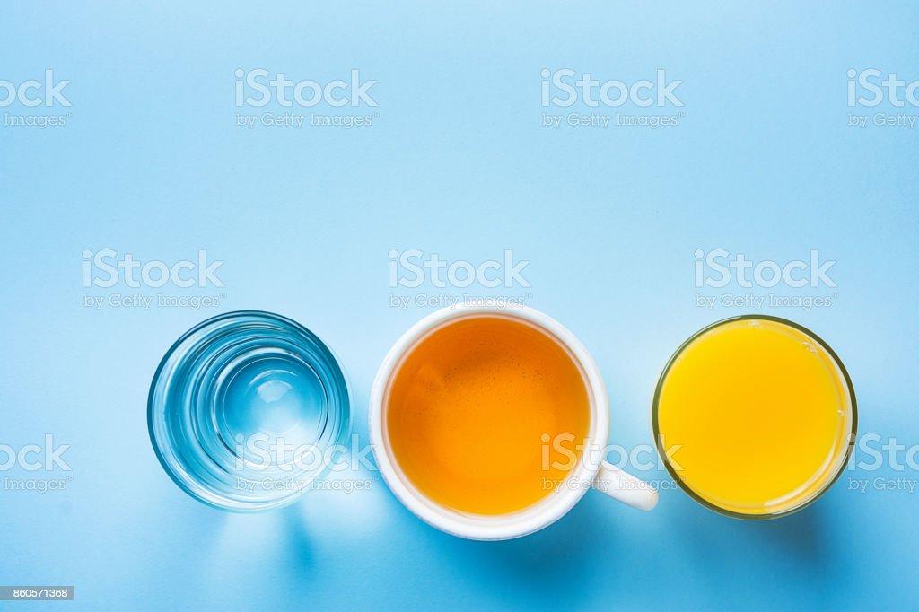Glass of Freshly Pressed Orange Citrus Juice Herbal Tea Water on Light Blue Background. Healthy Breakfast Drinks. Freshness Detox. Funky Hipster Modern Style Copy Space stock photo