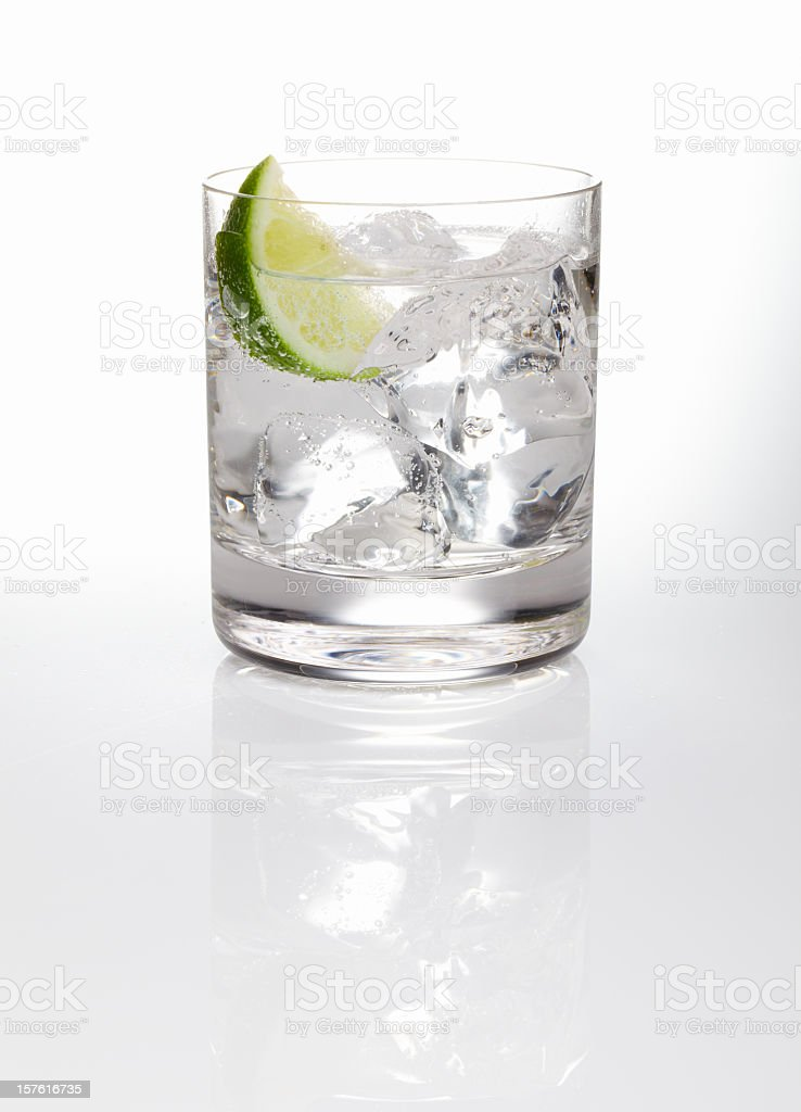 A glass of gin and tonic with ice and a slice of lime  royalty-free stock photo