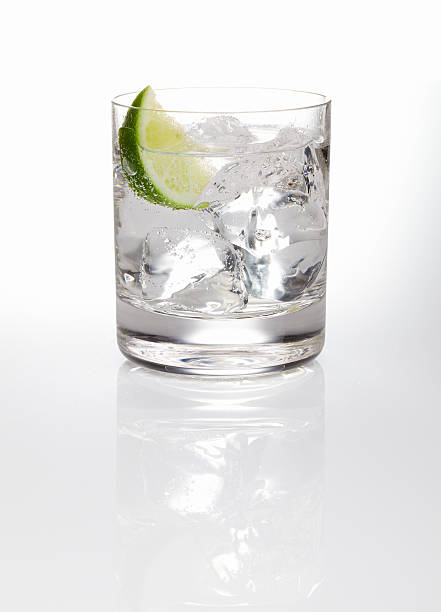 A glass of gin and tonic with ice and a slice of lime  Gin and tonic with wedge of lime shot on reflective white background. vodka stock pictures, royalty-free photos & images