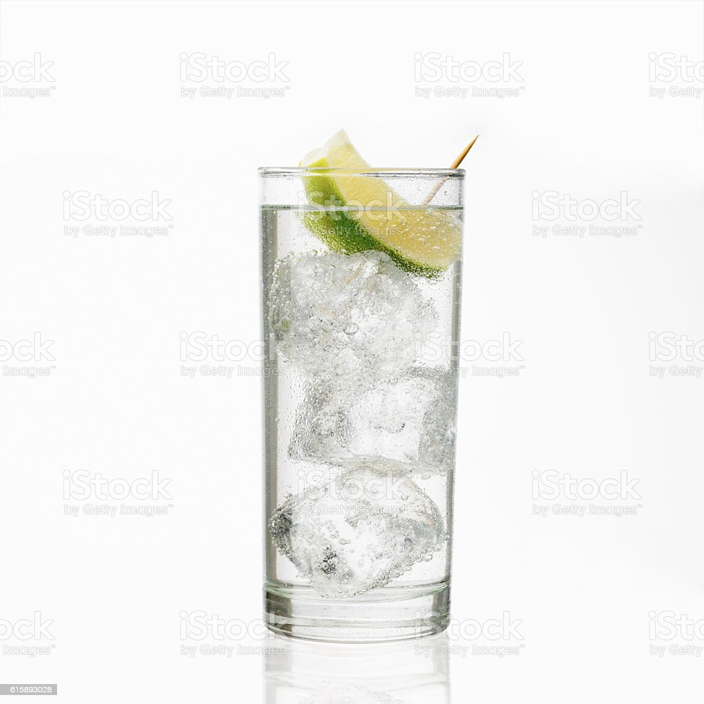 Glass of gin and tonic with ice and lime stock photo