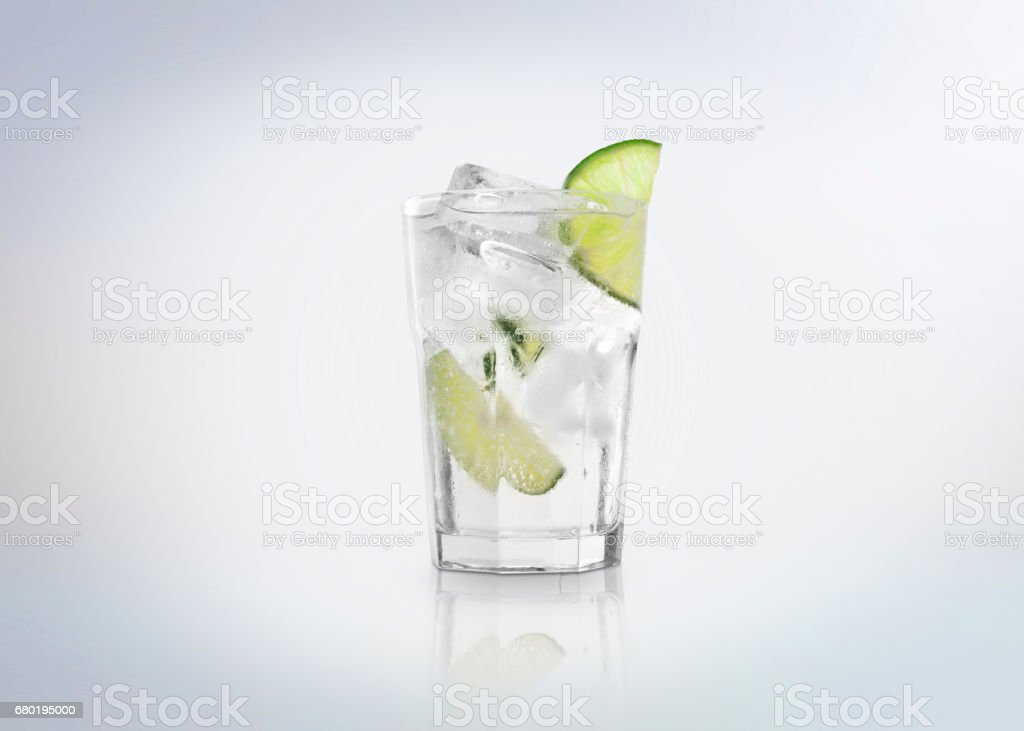 A glass of Gin Tonic cocktail  drink with ice cubes (on the rocks) and a slice of lime. stock photo