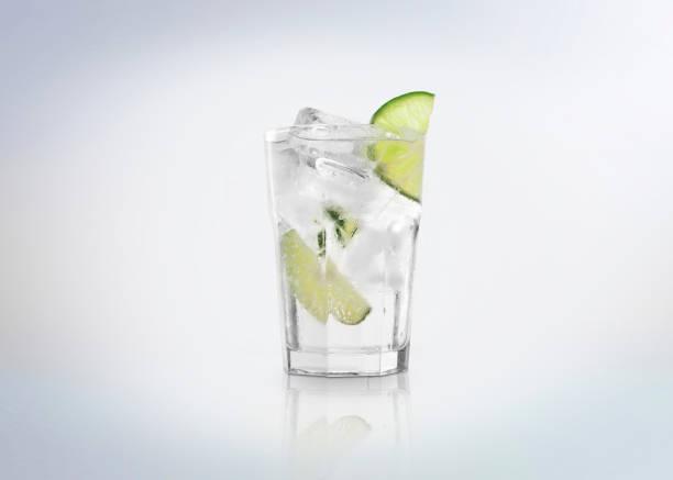 Un verre de cocktail de Gin Tonic avec des cubes de glace (sur les rochers) et une rondelle de citron vert. - Photo