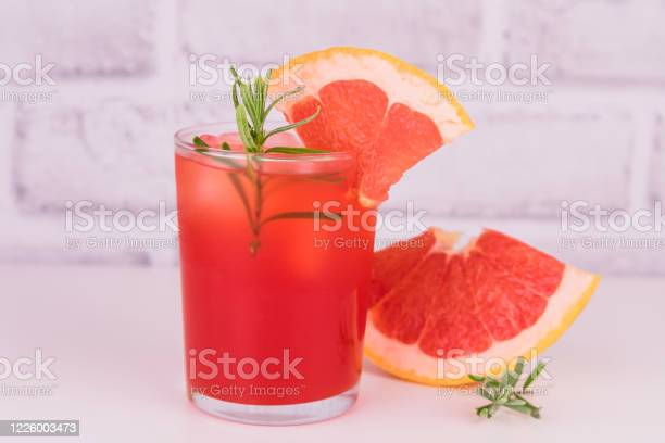 Photo of Glass of  grapefruit juice on a white background.