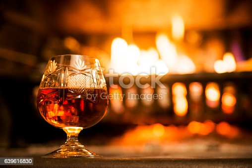 Brandy snifter warming before a glowing fire on an enjoyable and entertaining night out on the town