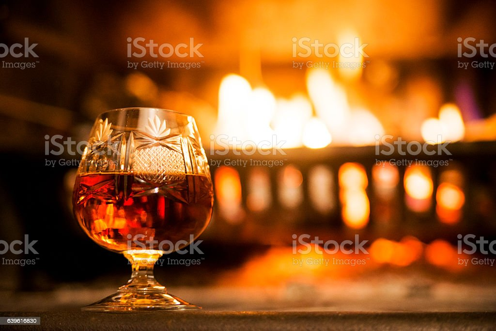 glass of hard liquor in front of the fireplace night stock photo