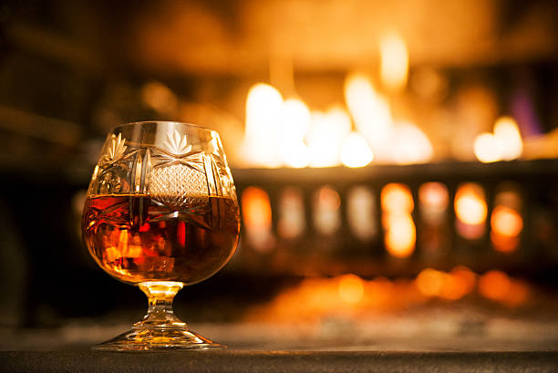 glass of hard liquor in front of the fireplace night - 干邑 白蘭地 個照片及圖片檔