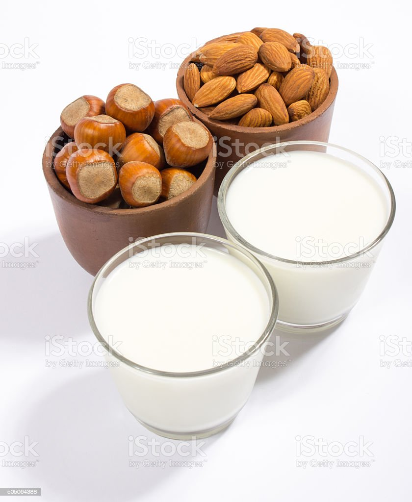 Glass of hazelnut milk and almond isolated on white background. stock photo