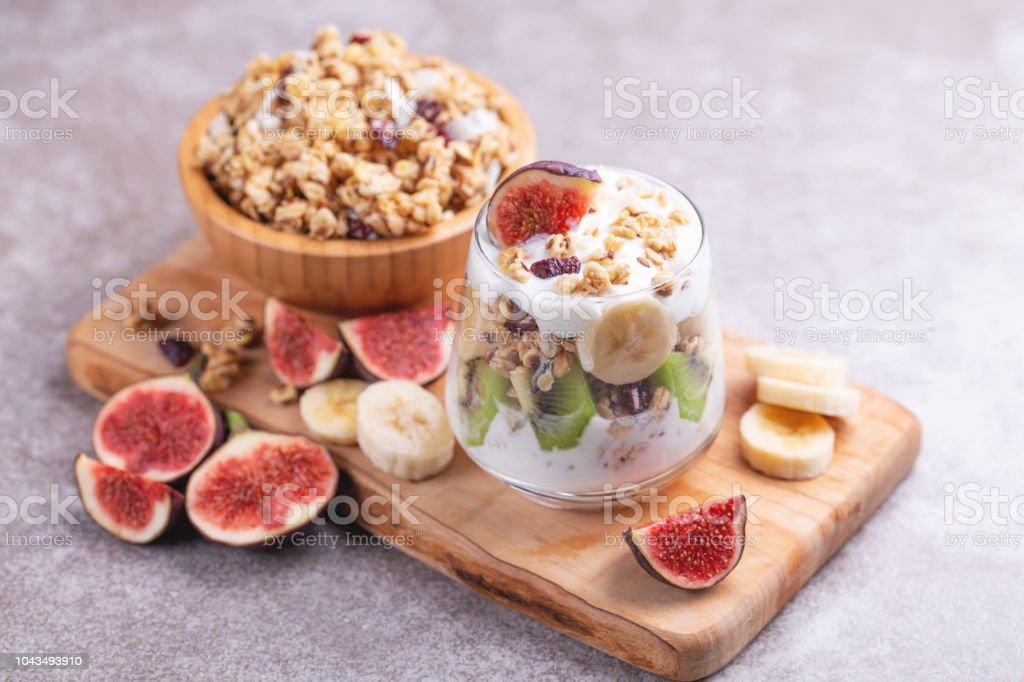 Glass of homemade granola with yogurt and fresh bananas and figs on grey slate background.