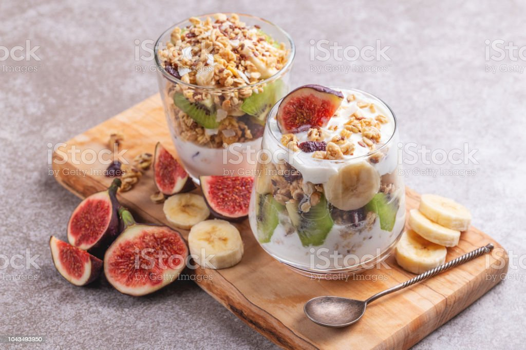 Glass of homemade granola with yogurt and fresh bananas and figs on grey slate background.  Horizontal view. Copy space