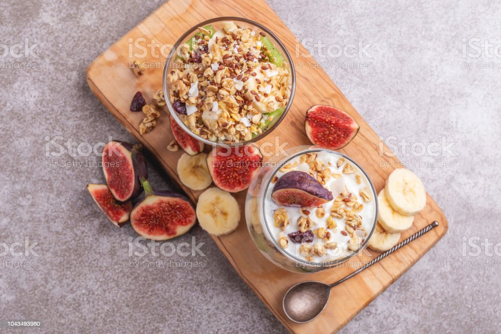 Glass of homemade granola with yogurt and fresh bananas and figs on grey slate background.  Top view. Copy space