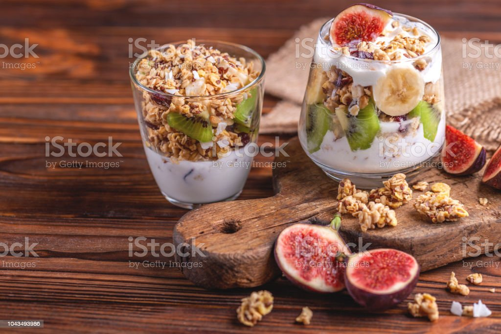 Glass of homemade granola with yogurt and fresh bananas and figs on wooden background.  Horizontal view. Copy space