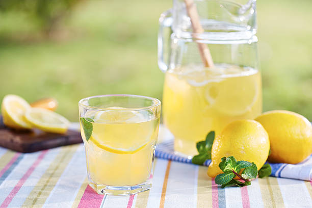 Glass of homemade lemonade Glass of homemade lemonade in a garden table lemonade stand stock pictures, royalty-free photos & images
