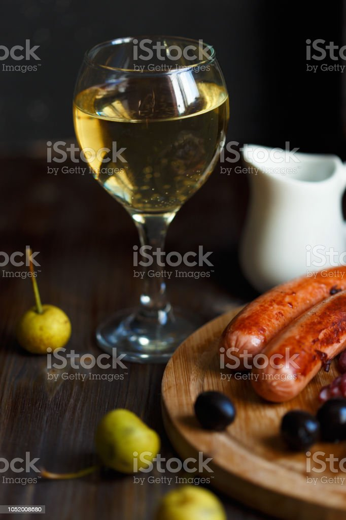 glass of homemade pear wine with a snack. Grilled sausages, cheese, olives. Menu and restaurant concept. stock photo