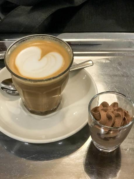 glas heißer kaffee latte kunst und schokolade sahne auf einem edelstahl-tablett - mokkatassen stock-fotos und bilder