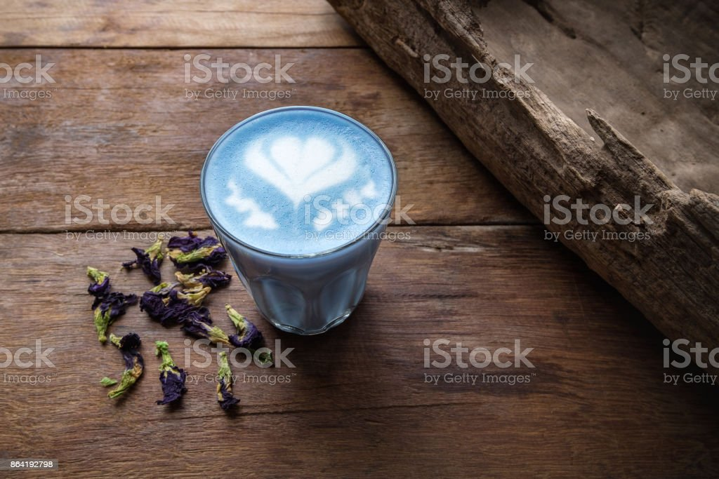 A glass of hot milk butterfly pea latte art  on the wooden table in coffee shop stock photo