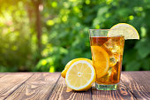 glass of ice tea with lemon on wooden table outdoors