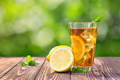 glass of ice tea with mint and lemon on wooden table outdoors