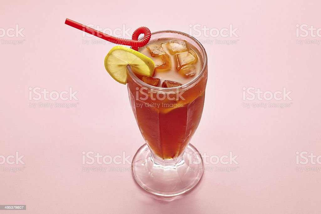 glass of cold ice tea with lemon on pink background