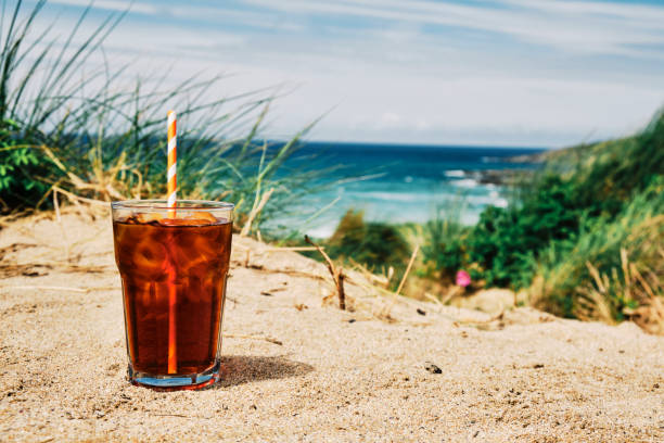 glass of iced black coffee on the sand dunes above fistral beach, newquay on a hot sunny summers day. - iced coffee stock pictures, royalty-free photos & images