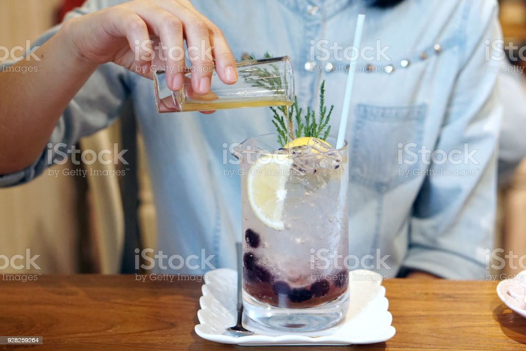 A glass of iced blueberry soda with lemon. stock photo