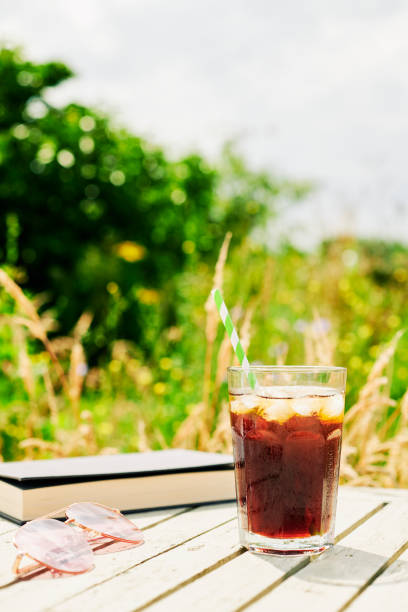 glass of iced coffee on a garden table on a hot sunny day. - iced coffee stock pictures, royalty-free photos & images