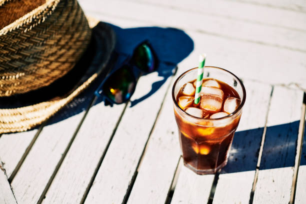 glass of iced coffee on a garden table, outdoors on a sunny summers day. - iced coffee stock pictures, royalty-free photos & images