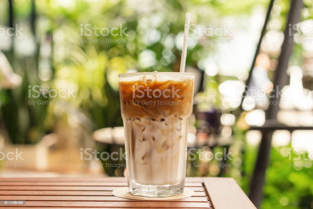 Glass of Iced coffee on the wood table, summer day, close up stock photo