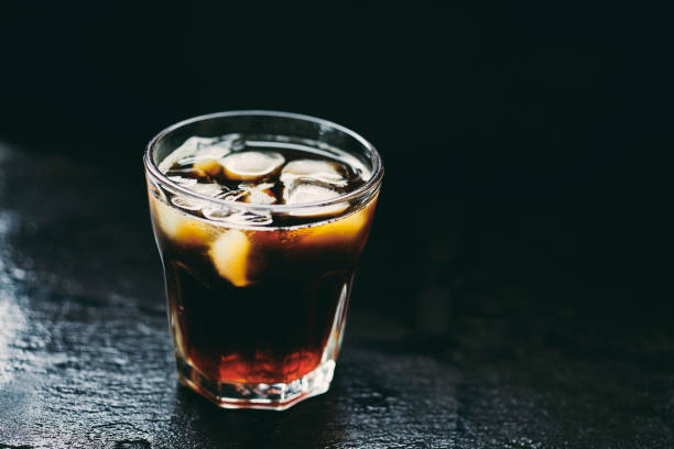 glass of iced cold brew coffee against a dark slate background. - iced coffee stock pictures, royalty-free photos & images