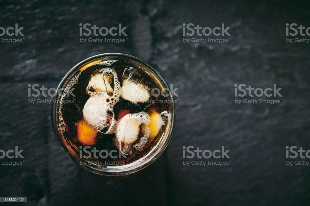 Glass of Iced Cold Brew Coffee against a dark slate background. stock photo
