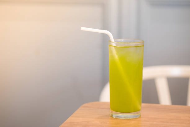 glas grüner eistee mit einem strohhalm auf holztisch - grüner tee koffein stock-fotos und bilder