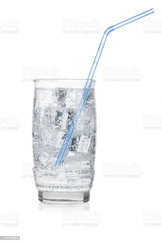 Glass of iced mineral water with straw isolated on white. royalty-free stock photo
