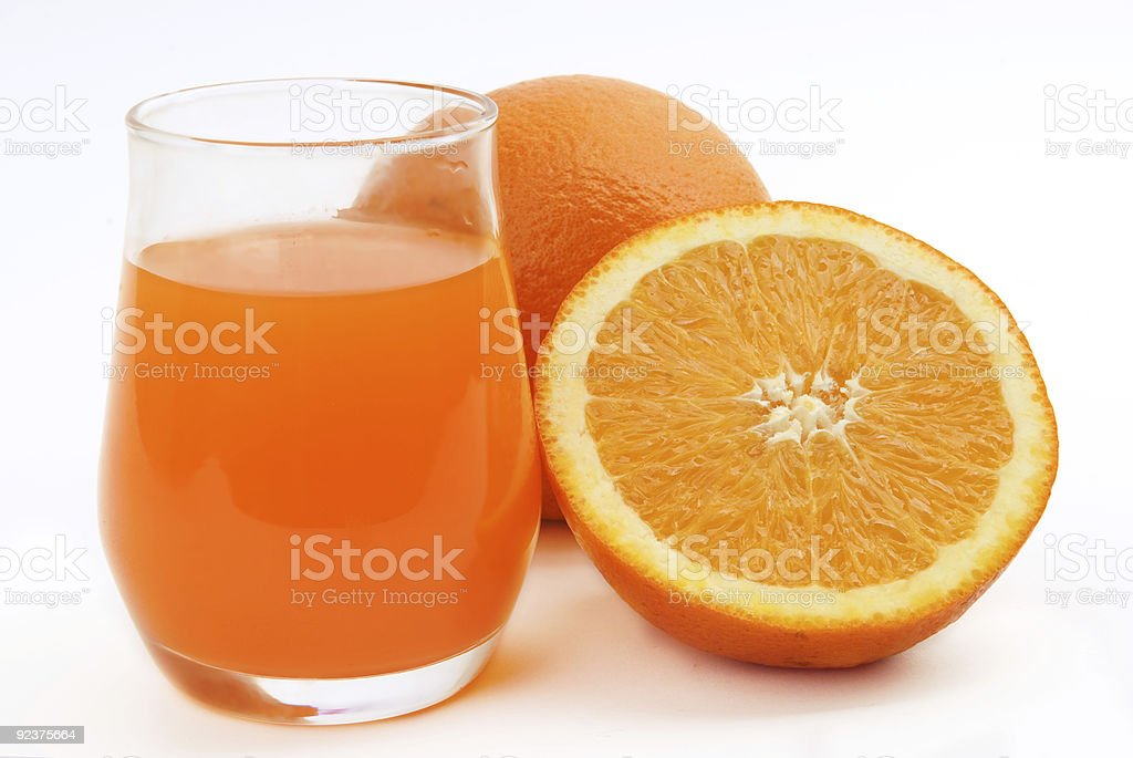 glass of  juice and some orange halves royalty-free stock photo