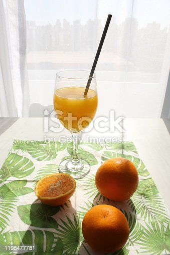 various oranges and glass with orange juice and metal straw