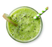 Glass of green kiwi smoothie with straw isolated on white background. Top view